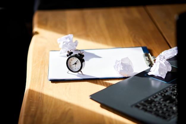 현대적인 작업 공간, 조명이 비치는 나무 사무실 책상, 시계가 있는 햇빛, 종이 한 장