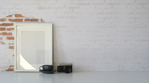 Modern workspace, blank poster frame and empty brick wall