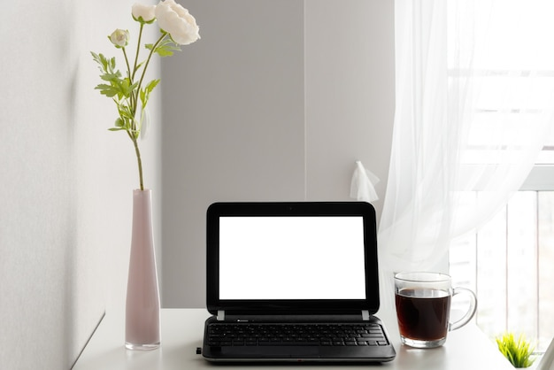 Modern workspace with blank screen laptop, frame, coffee cup and vase on white table against the background of a window and a light wall