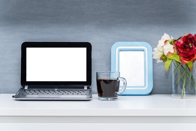 Modern workspace with blank screen laptop, frame, coffee cup and vase on white table with gray-blue wall background