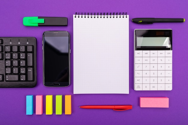 Modern workspace with calculator, smartphone and notebook on colorful background. top view.