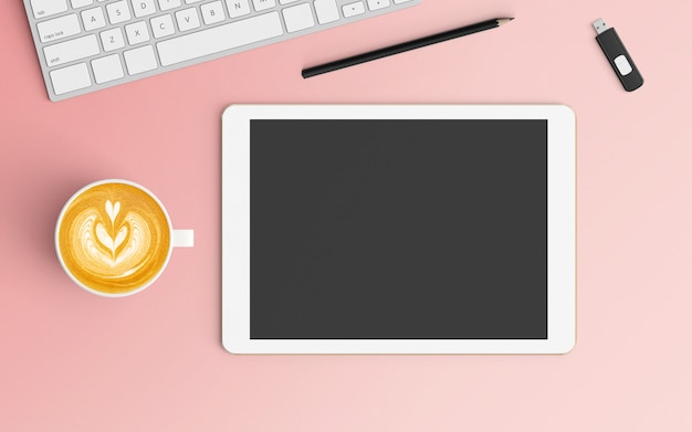 Modern workspace with coffee cup, keyboard and tablet on pink color
