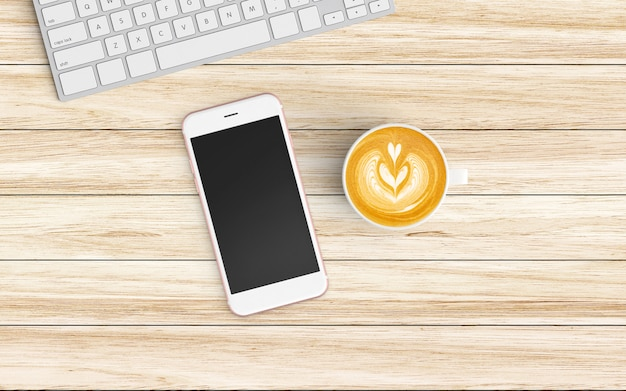 Modern workspace with coffee cup, notebook, tablet or smartphone and keyboard on wood