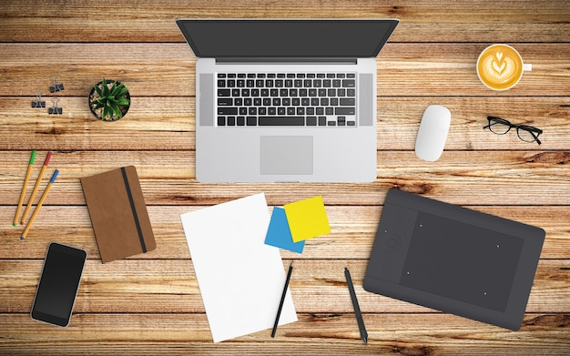 Modern workspace with coffee cup, paper, notebook, tablet or smartphone and laptop on wood