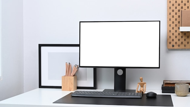Modern workspace with computer, empty photo frame and office supplies on white table.