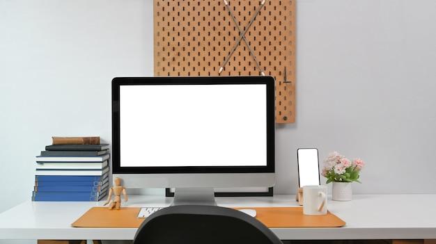 Современное рабочее пространство с компьютером, смартфоном и канцелярскими принадлежностями на белом столе.