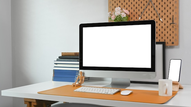 Modern workspace with computer, smart phone, coffee cup, books and office supplies on white desk.