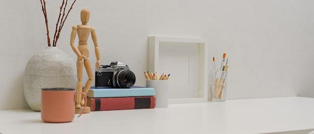 Современное рабочее пространство с копией пространства, кружка, инструменты рисования, камера, книги и украшения