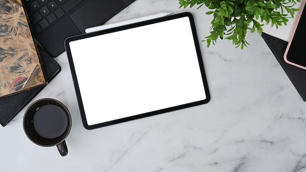Современное рабочее пространство с цифровым планшетом, кофейной чашкой, комнатным растением и блокнотом на мраморном столе.