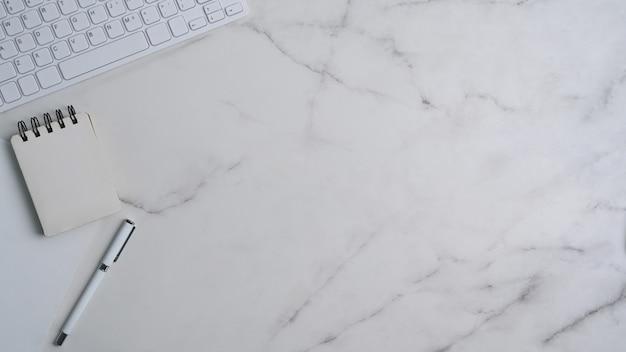 Современное рабочее пространство с клавиатурой, пустой записной книжкой, ручкой и копией пространства на мраморном фоне.