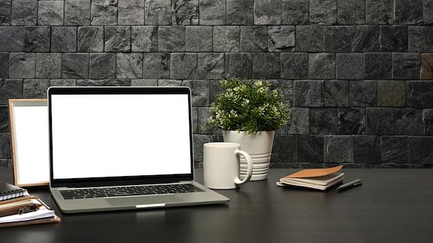 Современное рабочее пространство с портативным компьютером, кофейной чашкой и горшечным растением на черном столе с кирпичной стеной.