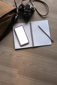 木製のテーブルに携帯電話、ノートブック、カメラ、バッグを備えたモダンなワークスペース