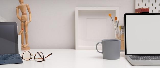 Modern workspace with mock up laptop, digital tablet, glasses, designer supplies and decorations
