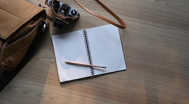 ノートブック、鉛筆、カメラ、木製のテーブルにバッグを備えたモダンなワークスペース
