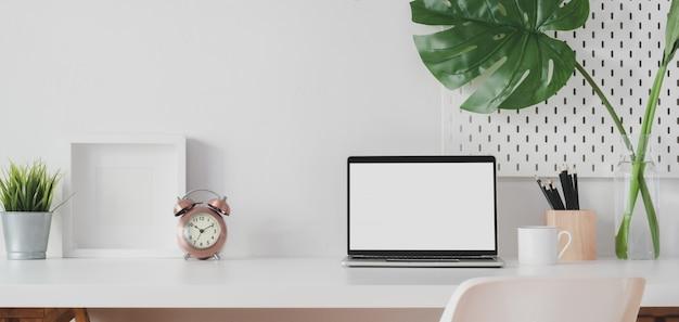 開いている空白の画面のラップトップコンピューターと装飾フレームのモダンなワークスペース
