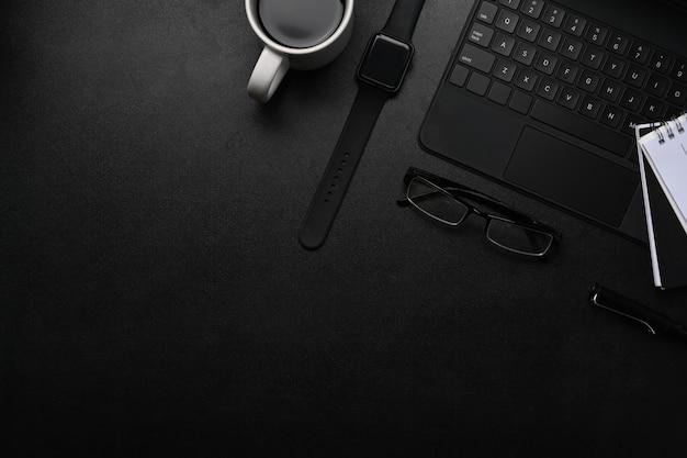 Современное рабочее пространство с умными часами, ноутбуком, клавиатурой и очками на черном столе.
