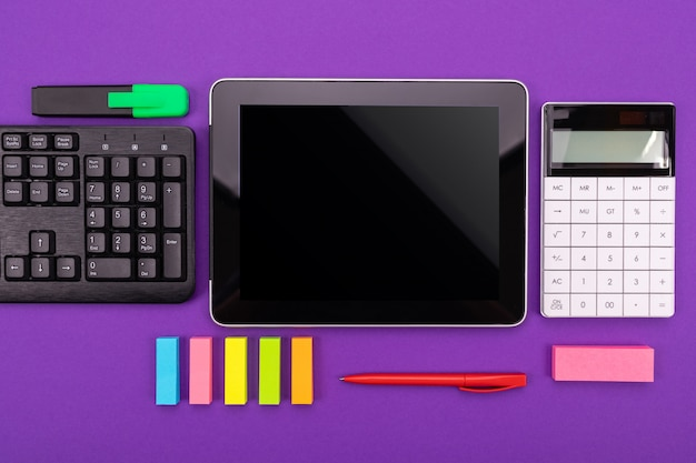 Modern workspace with tablet, keyboard and calculator on purple  . flat lay concept