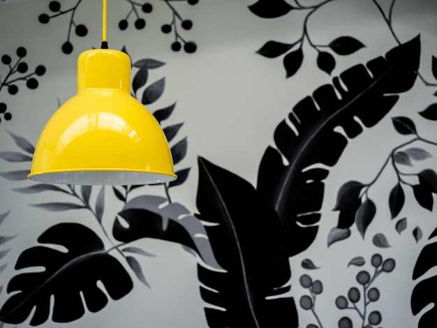 Modern yellow ceiling light on wallpaper, tropical palm leaves in black and white colors