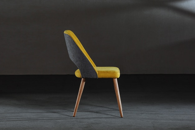 Modern yellow chair with wooden legs in a room under the lights