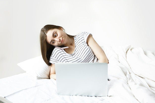 Modern young 20 year old female wearing striped pajamas while lying on white bedlinen, typing something using portable computer and having phone conversation