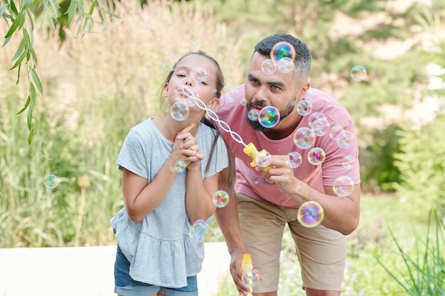 屋外でシャボン玉を吹く娘と楽しんでいる現代の若い大人の父