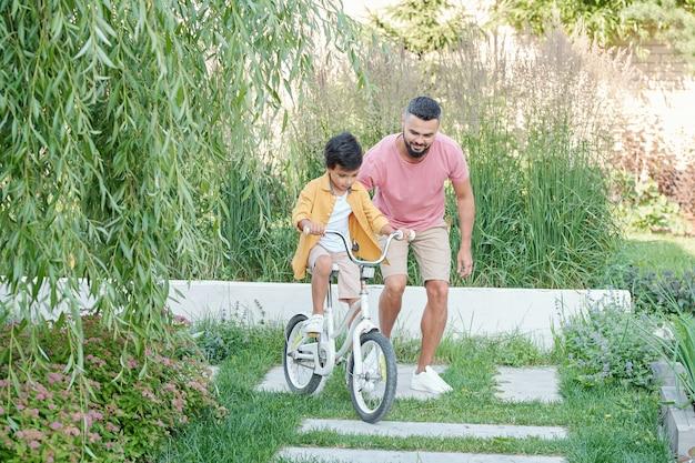 晴れた夏の日に裏庭で自転車に乗るように息子に教える現代の若い大人の父親