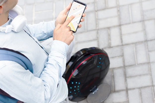 Modern young adult male businessman student freelancer with headphones, backpack and smartphone make route by navigator map for riding on ecological electric transport futuristic eco unicycle scooter