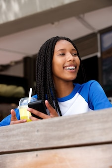 Modern young african woman with mobile phone sitting at cafe