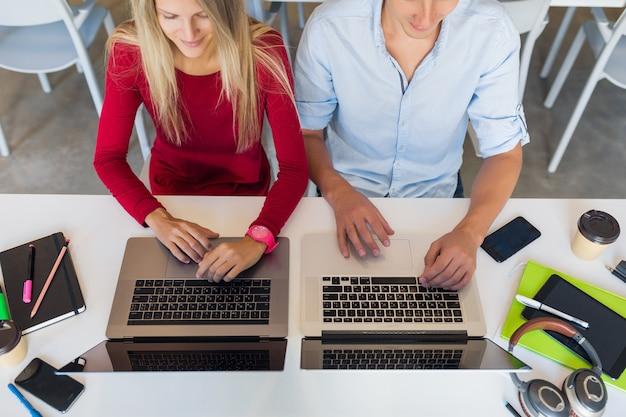 オープンスペースのコワーキング事務室でオンラインで一緒に働く現代の若い魅力的な人々
