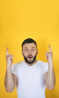 Современный молодой бородатый мужчина указывает вверх с какой-то идеей