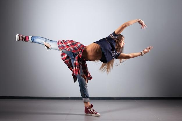 スタジオの背景にポーズをとって現代の若い美しいダンサー