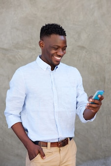 現代の若い黒人の男が携帯電話でテキストメッセージを読む