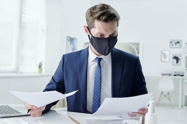 Современный молодой бизнесмен в тканевой маске сидит за столом в офисе и читает контракт при изучении условий