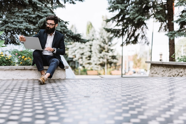 Modern young businessman sitting in the park looking at laptop