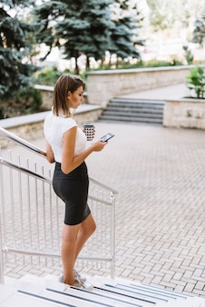 Modern young businesswoman standing on steps near the campus using smartphone