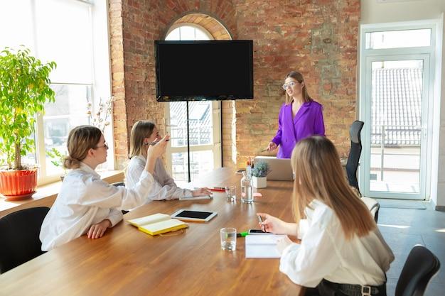 Современный. молодая кавказская бизнес-леди в современном офисе с командой.