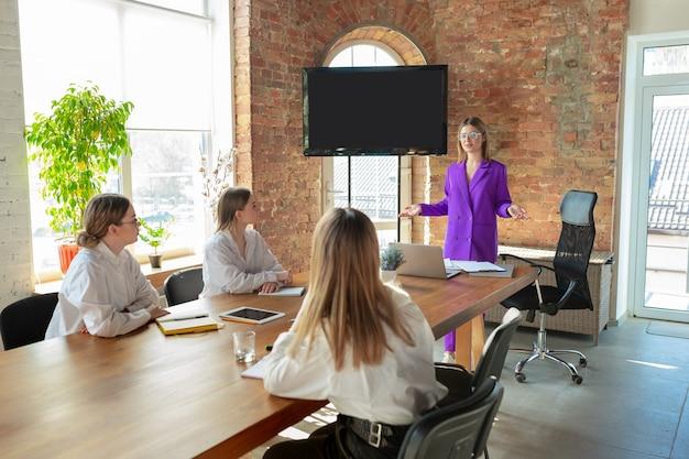 Moderno. giovane donna caucasica di affari in ufficio moderno con la squadra. incontro, assegnazione di compiti. donne al lavoro di front-office. concetto di finanza, affari, potere femminile, inclusione, diversità e femminismo