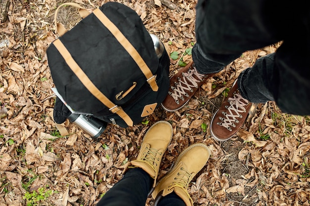 Modern young couple in hiking boots standing in the wood with travel bag