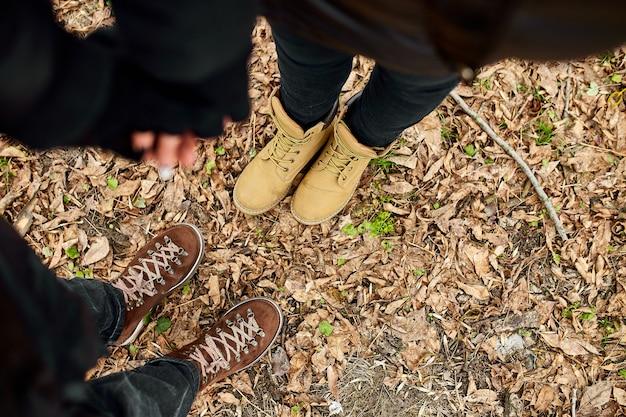 등산화를 신고 손을 잡고 있는 현대적인 젊은 부부는 숲에 떨어진 낙엽, 야외 여행 컨셉, 최고의 전망, 영원히 사랑, 발렌타인 데이.