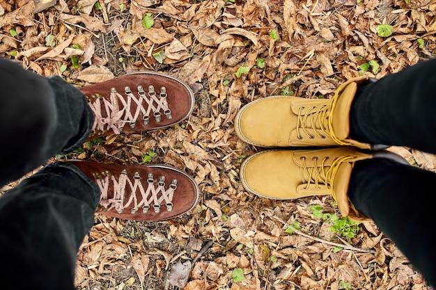 Современная молодая пара в походных ботинках стоит опавшие осенние листья в лесу