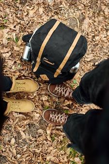 Современная молодая пара в походных ботинках, стоящих в лесу с дорожной сумкой