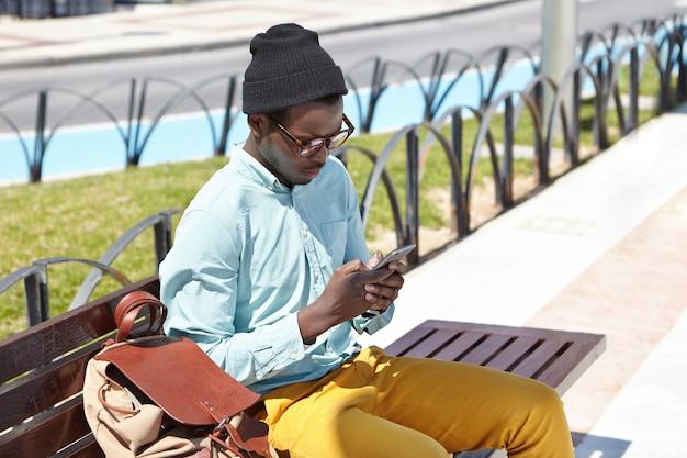 Moderna giovane hipster dalla pelle scura in elegante copricapo e occhiali da sole usando la città libera wi-fi su gadget elettronici all'aperto, seduto su una panchina di legno nel parco in attesa di amici prima di camminare