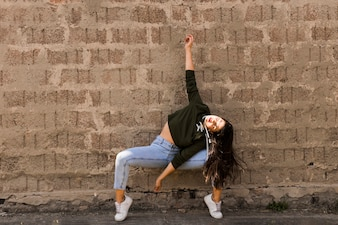 Modern young female dancer dancing in front of grunge wall
