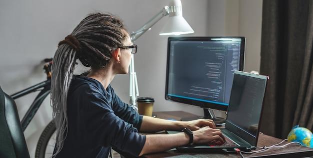 現代の若い女性プログラマーは、自宅のラップトップでプログラムコードを書いています