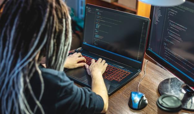 현대 젊은 여성 프로그래머는 집에서 노트북에 프로그램 코드를 작성하고 있습니다
