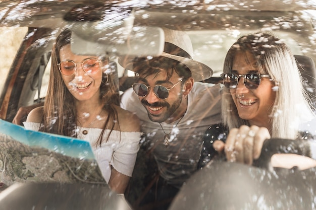 Modern young friends travelling in car looking at map