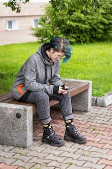 現代の若い女の子が路上でスマートフォンの画面を見てオンライン通信