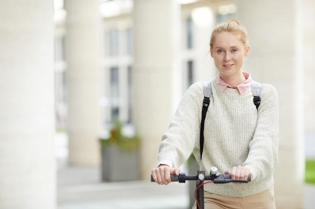 Современная молодая девушка езда скутер