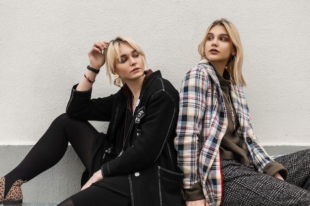 Современные молодые подружки фотомодели в модных винтажных куртках сидят рядом друг с другом на металлической трубе на улице