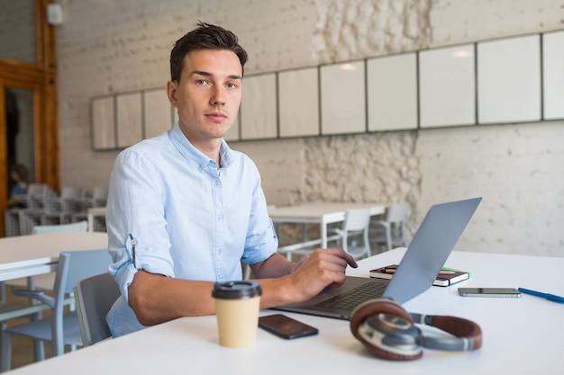 Современный молодой красавец сидит в офисе открытого пространства, работая на ноутбуке
